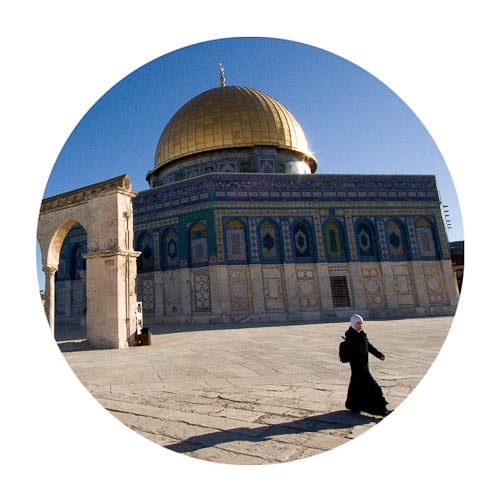 Photo of Muslim woman walking in front the Dome on the Rock.