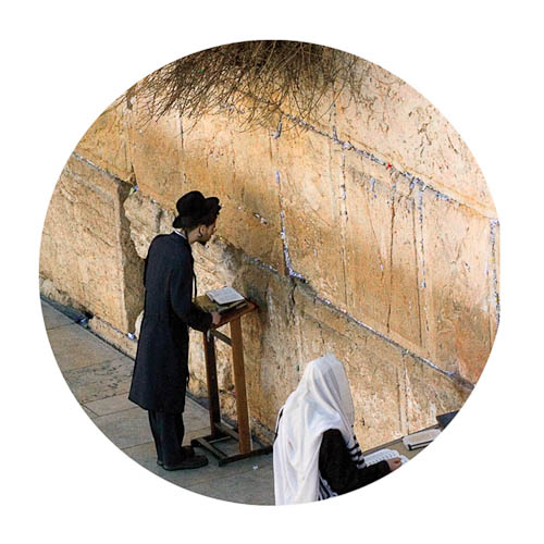 Photo of a of an orthodox Jewish man praying at the Kotel.
