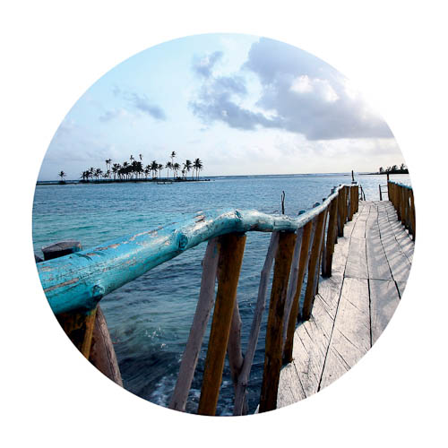 Photo of a faded blue rickety pier stretching off the Panamanian coast into the Caribbean sea.