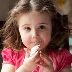 Photo of a stwo-year-old girl eating a cookie with powdered sugar on her face.