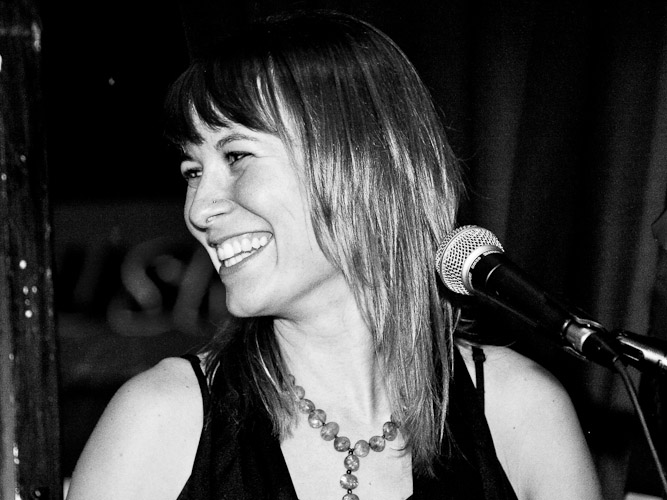 Black and white photo of a smiling singer, head turned to the side.