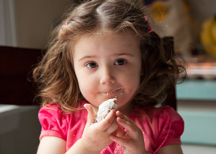 Photo of a two-year-old girl eating a cookie with powdered sugar on her face.