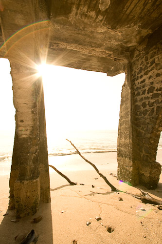 Photo of an old brick supporting structure, backlit from the sun rising over the ocean.