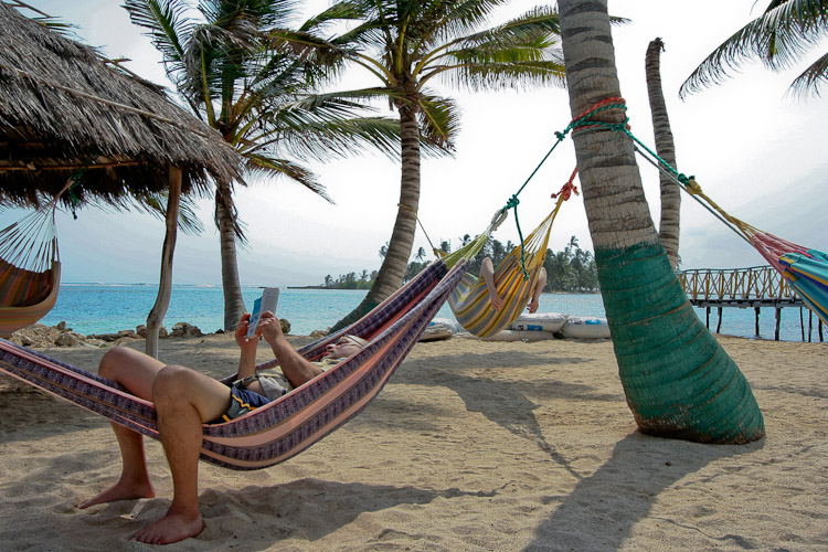 Photo of tourists lying in hammocks on a beach.