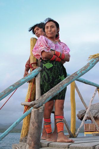 Photo of woman and boy on a boat dock. The woman is wearing brightly-patterned clothing with heavy beaded bands around her wrists and ankles.